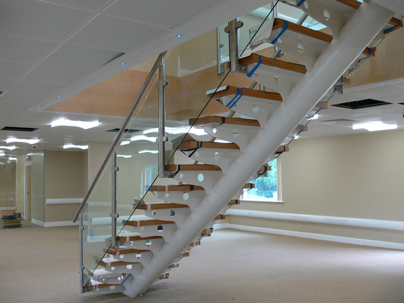 Central spine staircase, with stainless steel balustrade and glass panel infills. Wooden treads fitted on bespoke laser cut supports.</a>