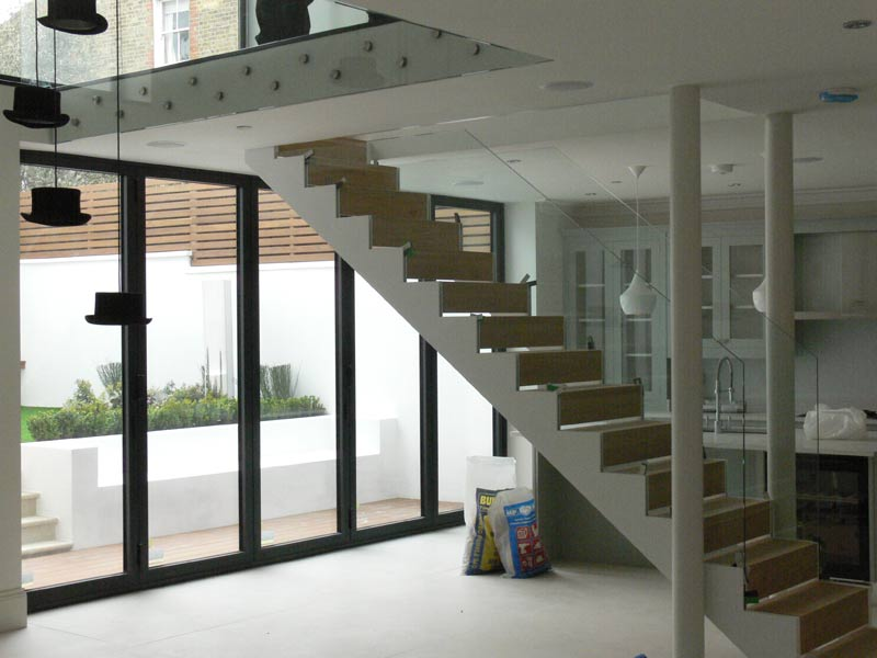 A steel staircase with double stringers, creating a channel for a minimalist glass frame. Finished with solid wooden treads.