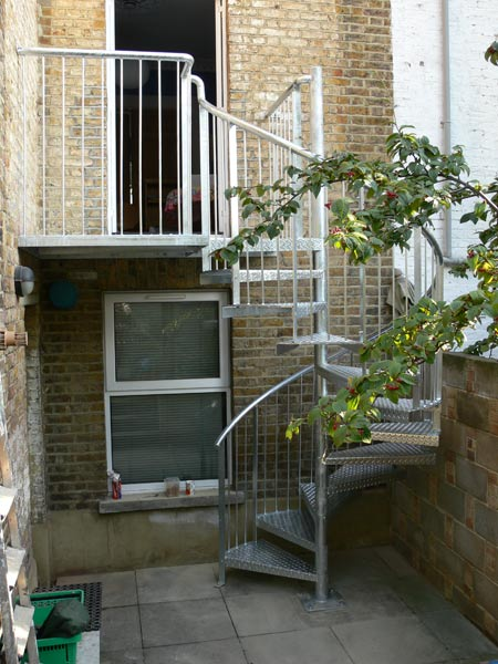 External spiral staircase, leading to a larger first floor platform, all with a galvanised finish.