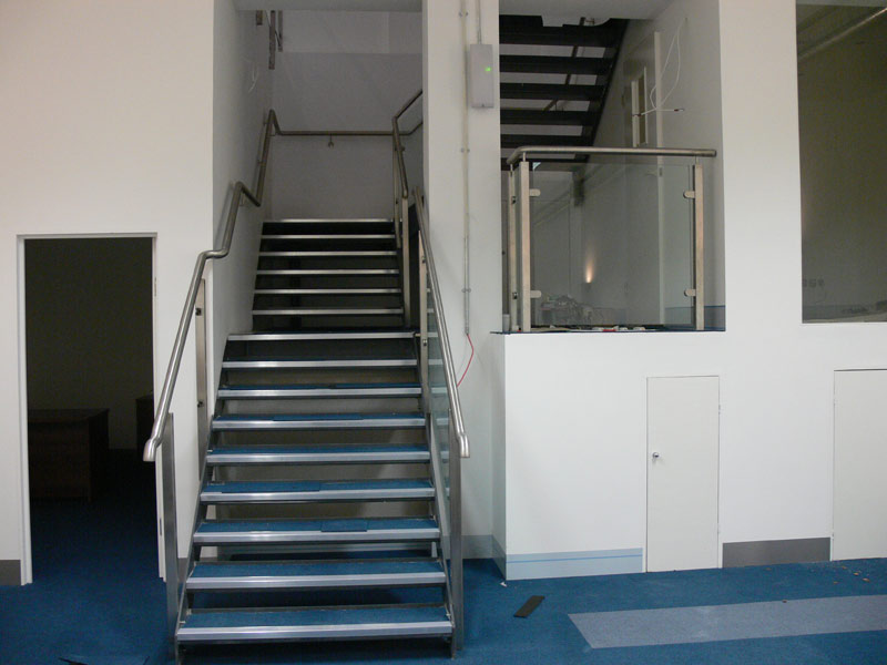 Stainless steel handrail and glass staircase with pan treads in-filled with concrete for a carpet finish. </br><a href='staircase2.html'>Click here to see more pictures of this staircase!</a>